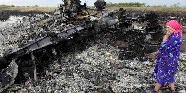 Une Ukrainienne regarde les débris du Boeing de la Malaysia Airlines à Grabove le 19 juillet