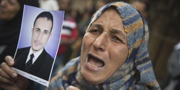Une femme montre le portrait d'un condamné à mort en