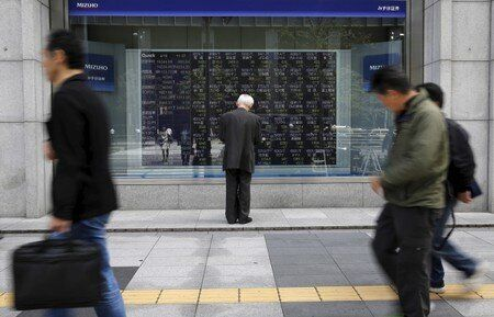 Man looks at a stock quotation board outside a brokerage in