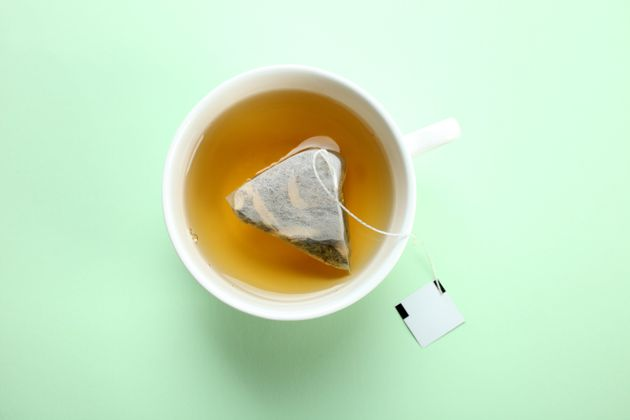 Mint tea bag in a cup on a mint pastel background. Top
