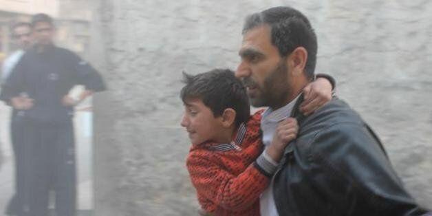 Un Syrien et ses enfants fuient le site d'un bombardement à Alep, le 16 novembre