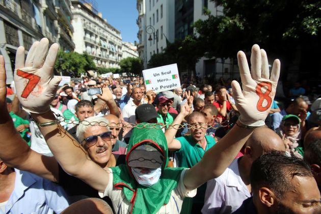 A demonstrator raises chained hands during a protest demanding social and economic reforms, as well as...