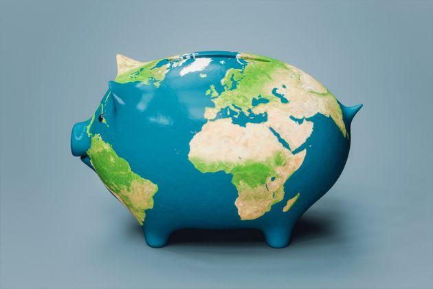 World map textured piggy bank on pale blue