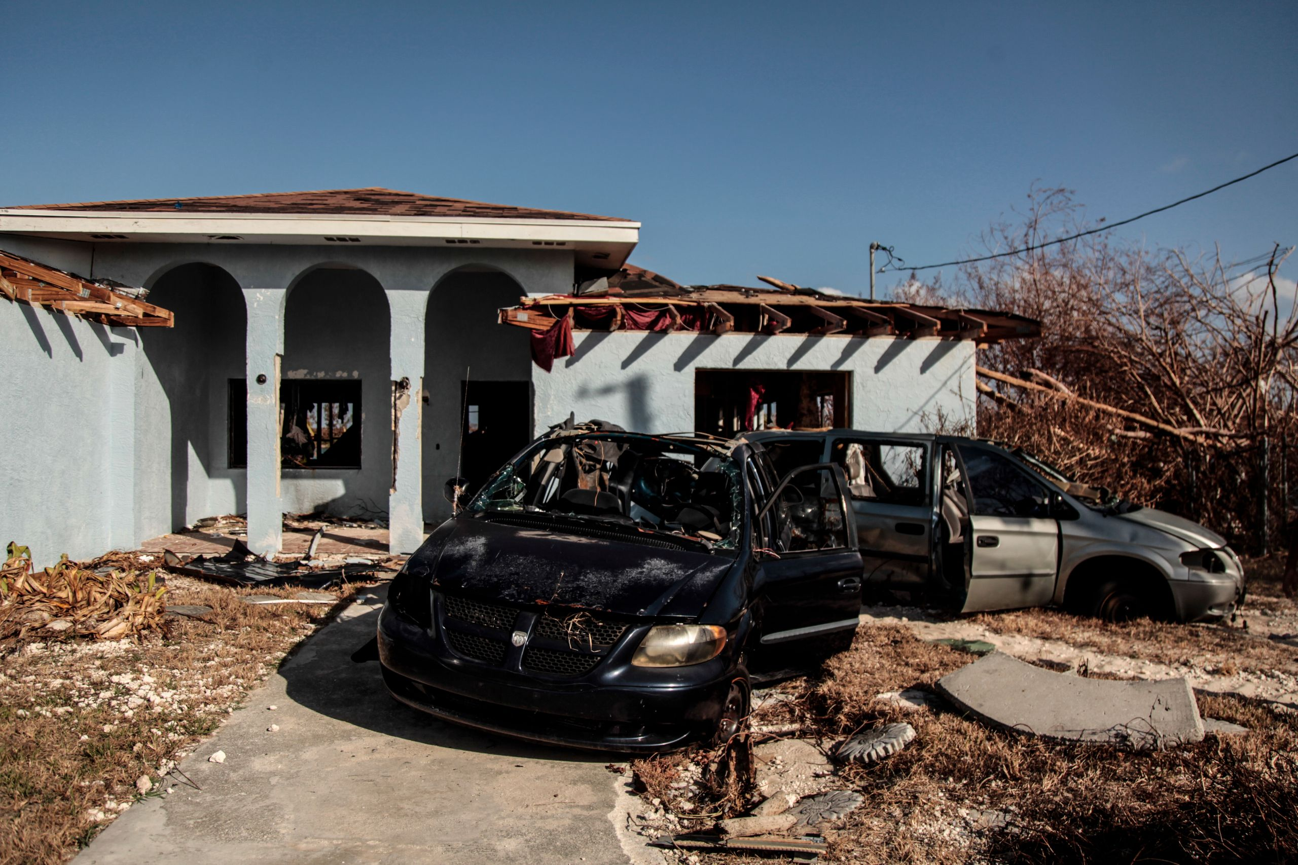 Crumpled vehicles sit outside Pastor Raymond Simozne's home in Freeport, Grand Bahama,.