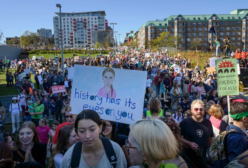 A drawing of Greta Thunberg is seen on a protest sign as thousands march on the property of Nova Scotia...
