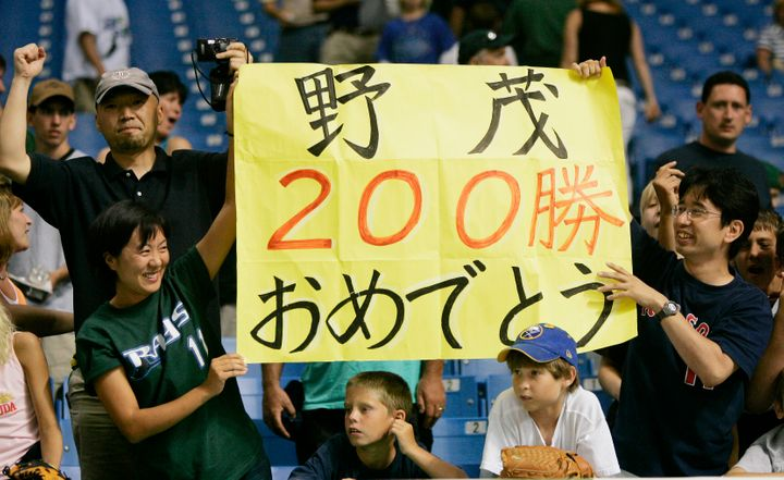 Fans hold up signs congratulating Tampa Bay Devil Rays pitcher Hideo Nomo on his 200th victory at Tropicana Field in St. Pete