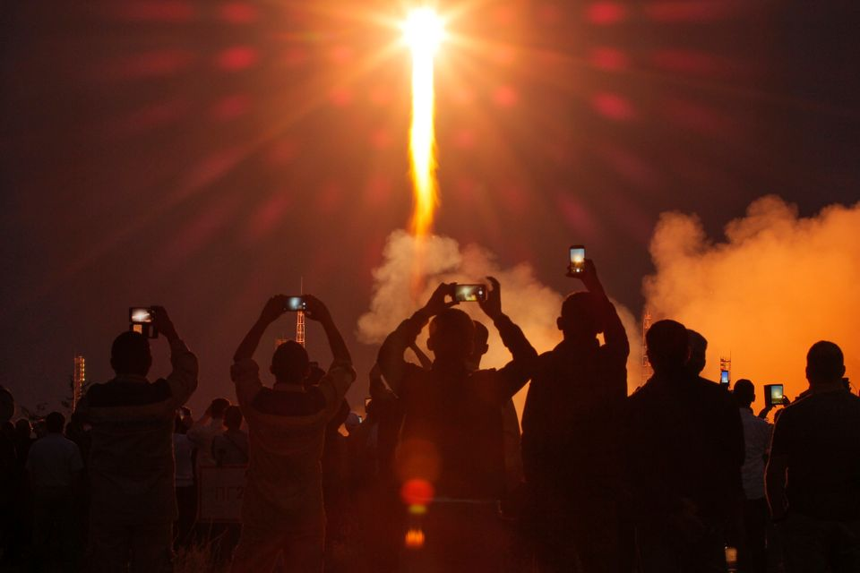 People watch the launch of the Soyuz-FG rocket booster with Soyuz MS-15 space ship carrying a new crew to the International Space Station, ISS, at the Russian leased Baikonur cosmodrome, Kazakhstan, Wednesday, Sept. 25, 2019. The Russian rocket carries U.S. astronaut Jessica Meir, Russian cosmonaut Oleg Skripochka, and United Arab Emirates astronaut Hazza Almansoori. (AP Photo/Dmitri Lovetsky)