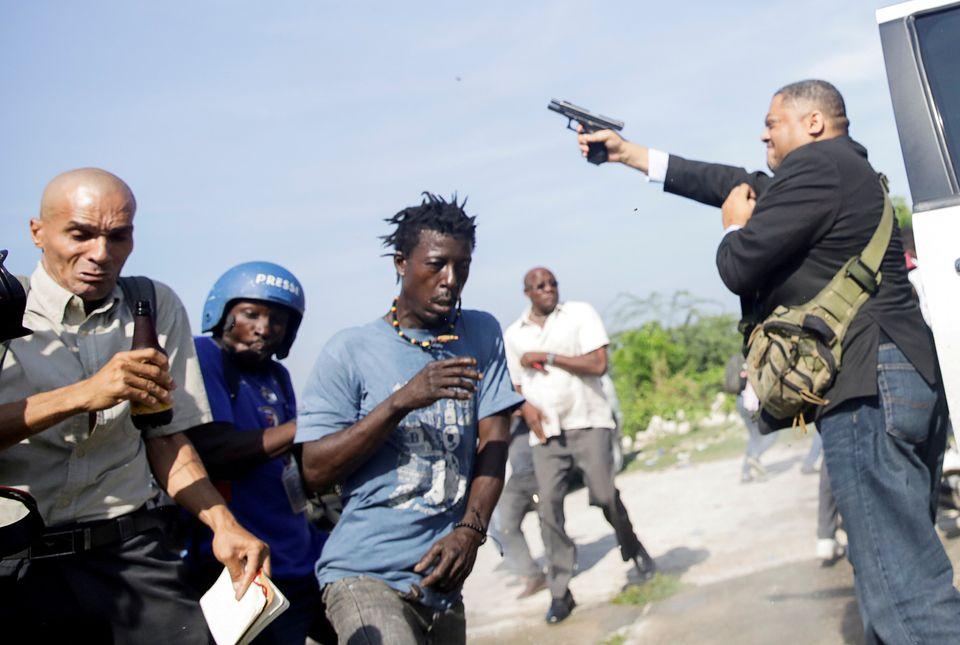 Άνθρωποι τρέχουν πανικόβλητοι καθώς ο Γερουσιαστής της Αϊτής,Jean Marie Ralph Fethiere, πυροβολεί στον αέρα, τραυματίζοντας τονChery Dieu-Nalio, φωτογράφο του Associated Press, την Δευτέρα.