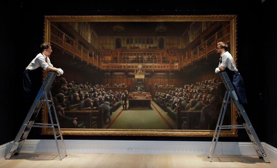 Υπάλληλοι του οίκου Sotheby κοιτάζουν τον πίνακα του καλλιτέχνη Bansky που βρίσκεται εκτεθειμένο σε αίθουσα δημοπρασιών του οίκου στο Λονδίνο, την Παρασκευή.