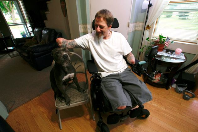 In this Aug. 16, 2019 photo, Greg Manteufel pets his dog Ellie at his home in West Bend,