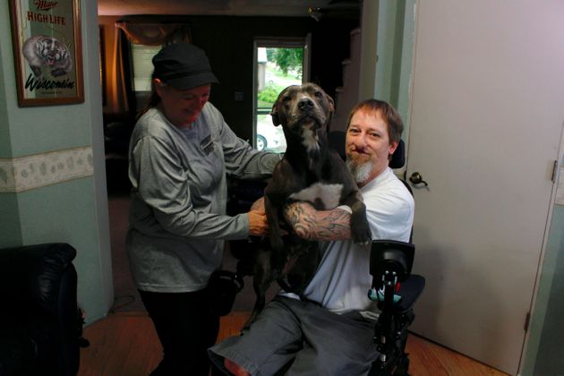 In this Aug. 16, 2019 photo, Greg Manteufel takes his dog Ellie from his wife Dawn Manteufel at their...