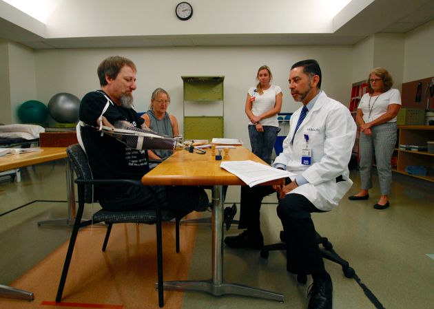 In this Aug. 19, 2019 photo, Greg Manteufel tries out a new prosthetic arm during occupational therapy...