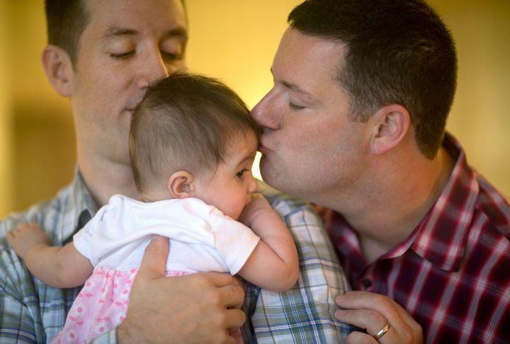 Imagen de archivo de dos padres junto a su hija.