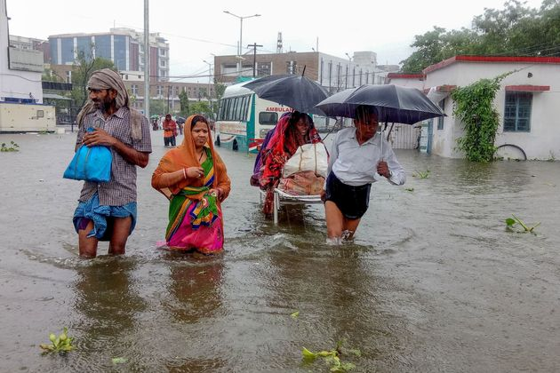 TOPSHOT - Patients wade through floodwaters on their way to hospital during heavy monsoon rain in Patna...