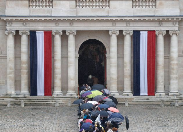 Le cercueil de Jacques Chirac, couvert de bleu blanc rouge, et entouré de drapeaux français...