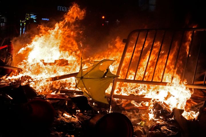 An umbrella burns after protesters set fire on steel barricades at a main street in Hong Kong. (AP Photo/Vincent Yu)