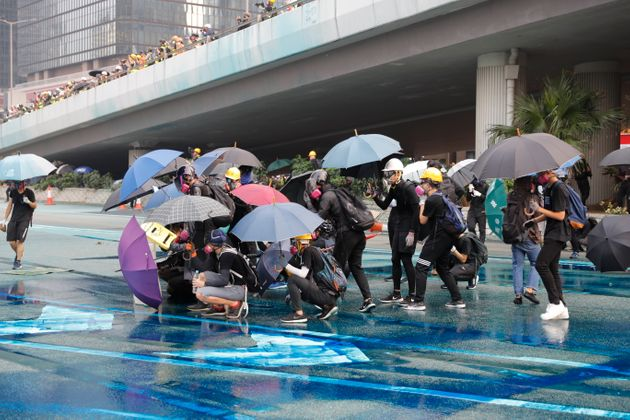 Police spray blue colored water on protestors Hong Kong, Sunday, Sept. 29, 2019. (AP Photo/Vincent