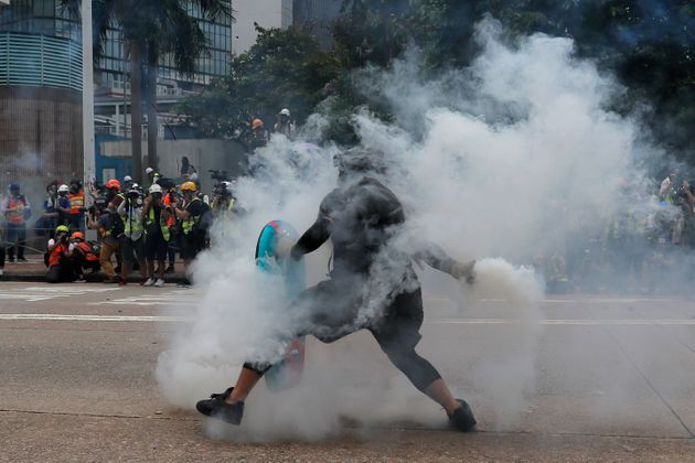 A protester throws a tear gas round back at police during the demonstration in Hong Kong. (AP Photo/Kin