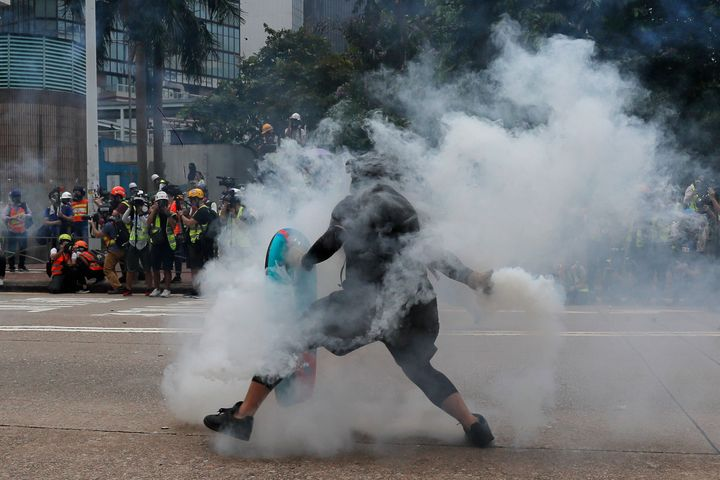 A protester throws a tear gas round back at police during the demonstration in Hong Kong. (AP Photo/Kin Cheung)