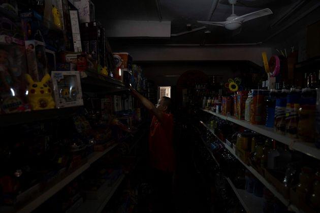El dueño de una tienda en el centro de Santa Cruz coloca luces provisionales mientras espera a que se...