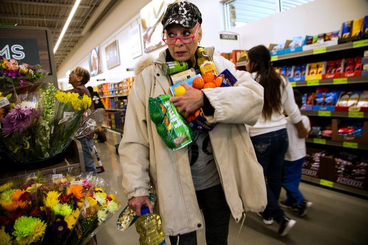 Janelle Myers fills her arms with groceries during the grand opening of Aldi food market on March 24, 2016 in Moreno Valley, California.