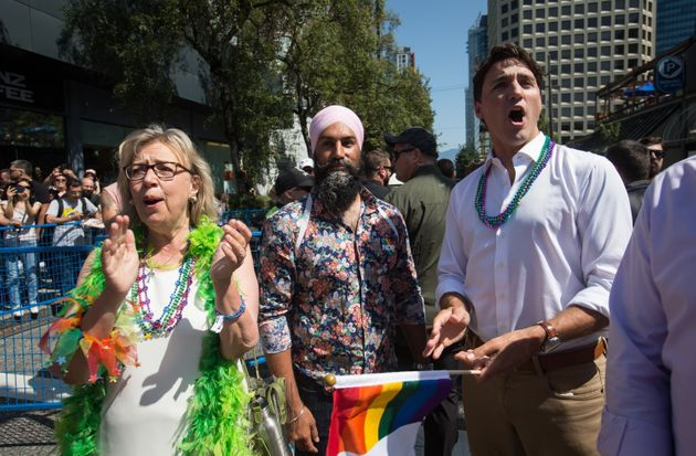 Liberal Leader Justin Trudeau, right, cheers while waiting to march in the Vancouver Pride Parade with...