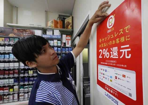 消費税率引き上げに伴い、キャッシュレス決済でのポイント還元を知らせるポスターを貼るコンビニの店員=10月1日未明、東京都品川区