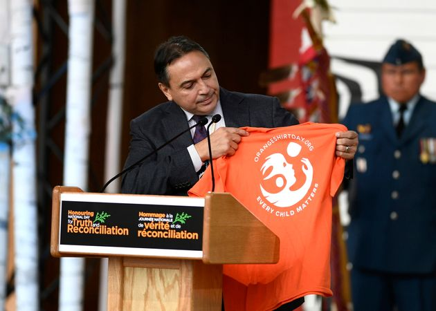 National Chief of the Assembly of First Nations Perry Bellegarde holds up an Orange Shirt Day t-shirt...