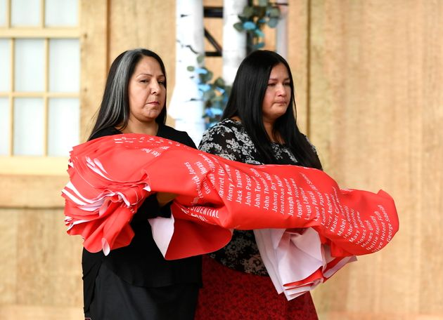 Joyce Hunter and Stephanie Scott, staff at the National Centre for Truth and Reconciliation, lay down...
