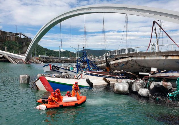 Rescuers work near the site of a collapsed bridge in Nanfangao, eastern Taiwan. Tuesday, Oct. 1,