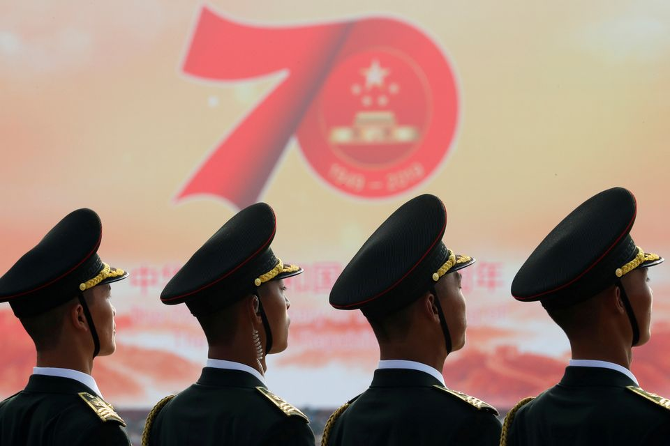 Soldiers of People's Liberation Army (PLA) are seen in front of a sign marking the 70th founding anniversary...