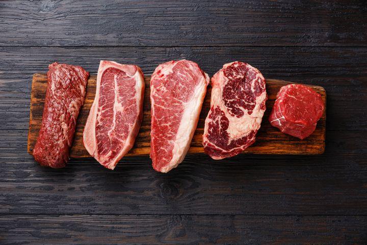 Variety of Raw Black Angus Prime meat steaks Machete, Blade on bone, Striploin, Rib eye, Tenderloin fillet mignon on wooden board copy space