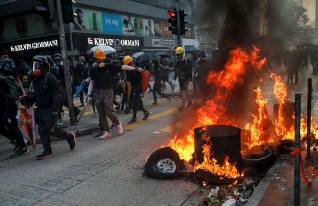 Anti-government protesters set tires on fire as they occupied a road during a protest on China's National...