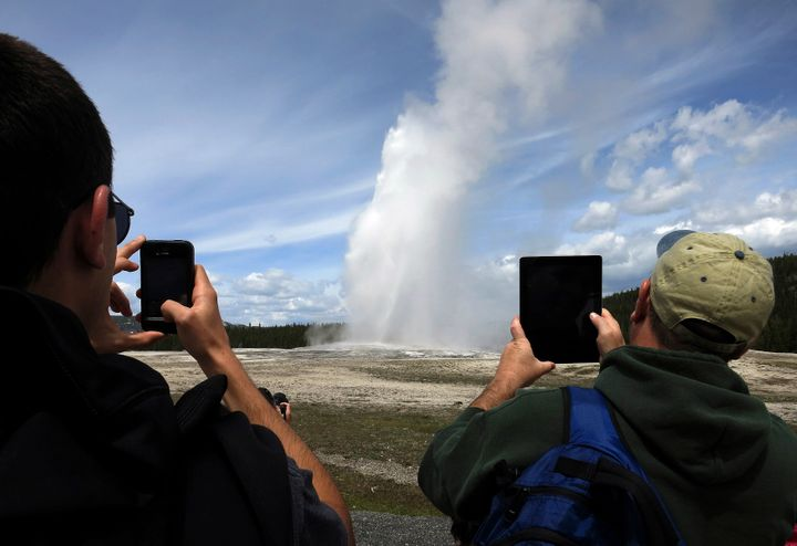 People use phones and tablets to photograph Old Faithful geyser erupting in Yellowstone National Park. The geyser's stea