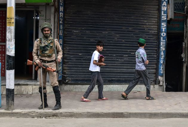 Children walk past a paramilitary trooper during restrictions in Srinagar,