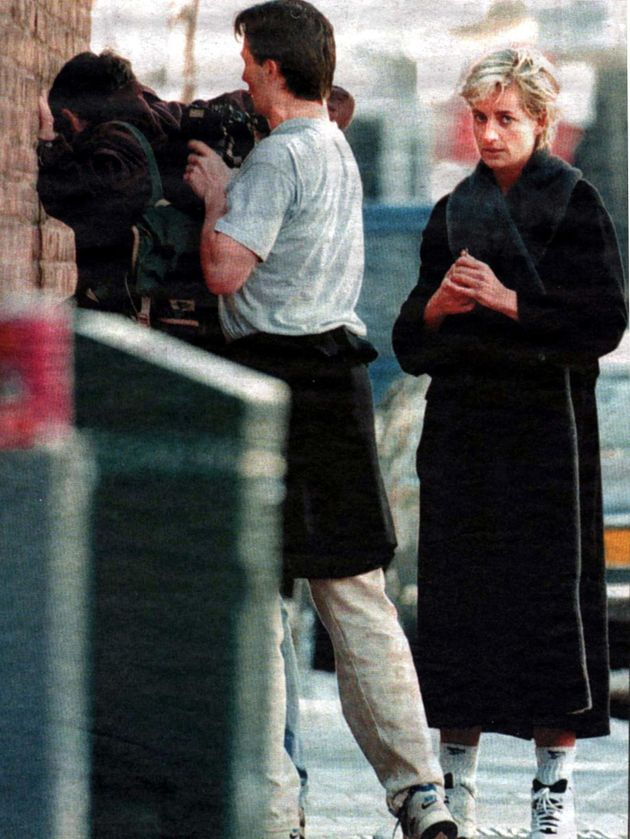 A passerby relieves photographer Brendan Beirne of the pictures he took of Diana exiting a gym in April...
