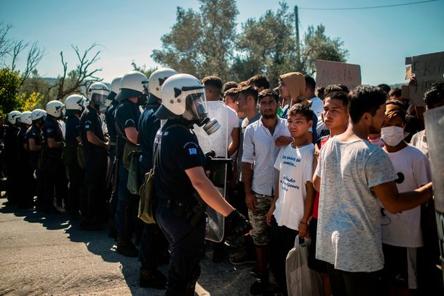 Refugees and migrants stand in front a riot police during in a demonstration against their living conditions...