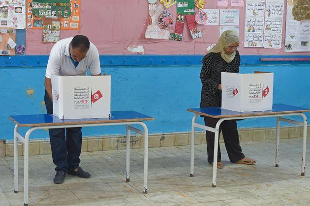 Des votants remplissent leur bulletin pour le premier tour de l'élection présidentielle à Ben Arous en...