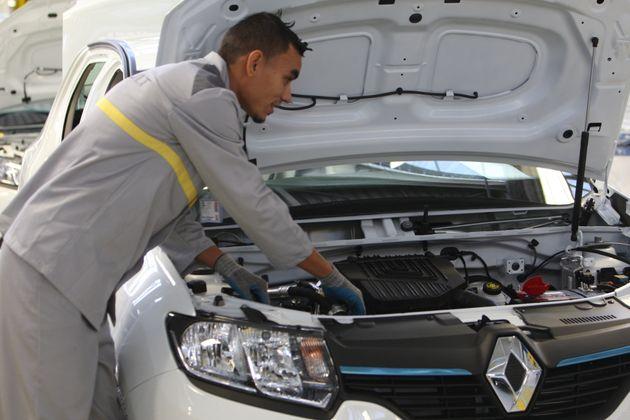 Ouvrier algérien travaillant sur un véhicule sur une chaine de montage lors de l'inauguration de l'usine...