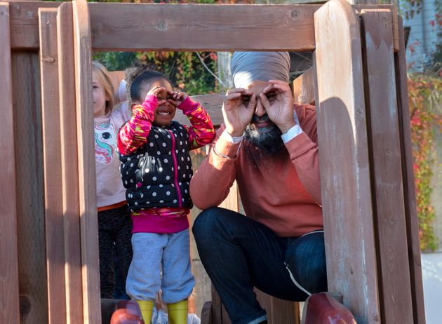 NDP Leader Jagmeet Singh and a young girl imitate the cameras as they stand on a play structure during...