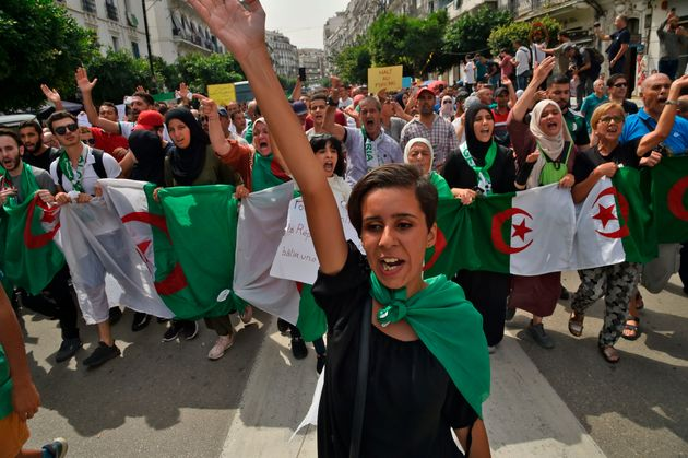 Algerian demonstrators carrying national flags chant slogans as they take part in a rally in the streets...