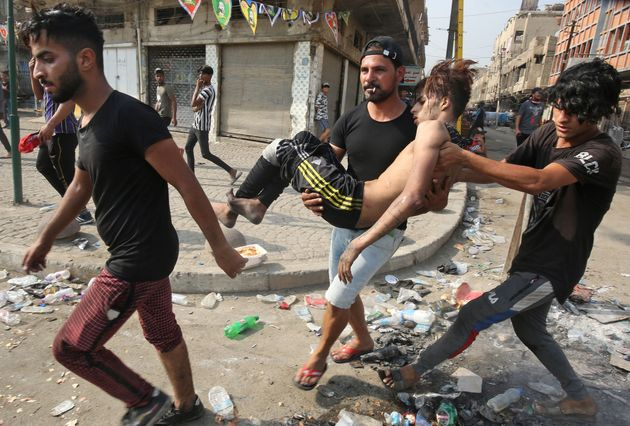 Youths carry away a protester injured during clashes with riot police amidst demonstrations against state...