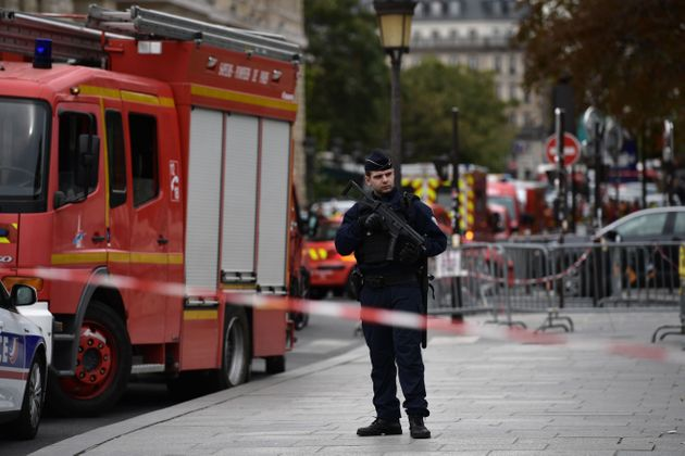 A policeman stands next to firefighter vehicles near where four officers were killed in a knife
