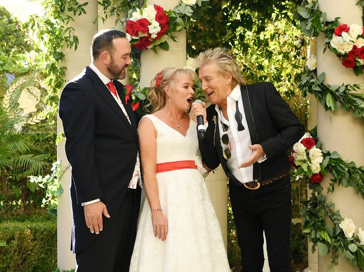 Rod Stewart and bride Sharon Cook sing while groom Andrew Aitchison looks on in delight.