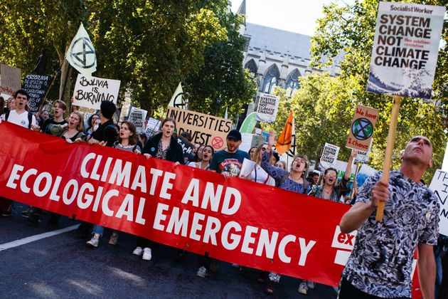 Extinction Rebellion activists group hold a banner and placards at a climate strike in