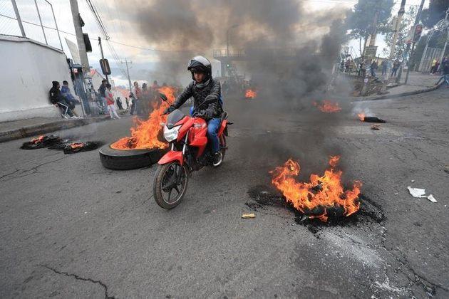 Un motociclista transita por una calle bloqueada con llantas encendidas este jueves durante una jornada...