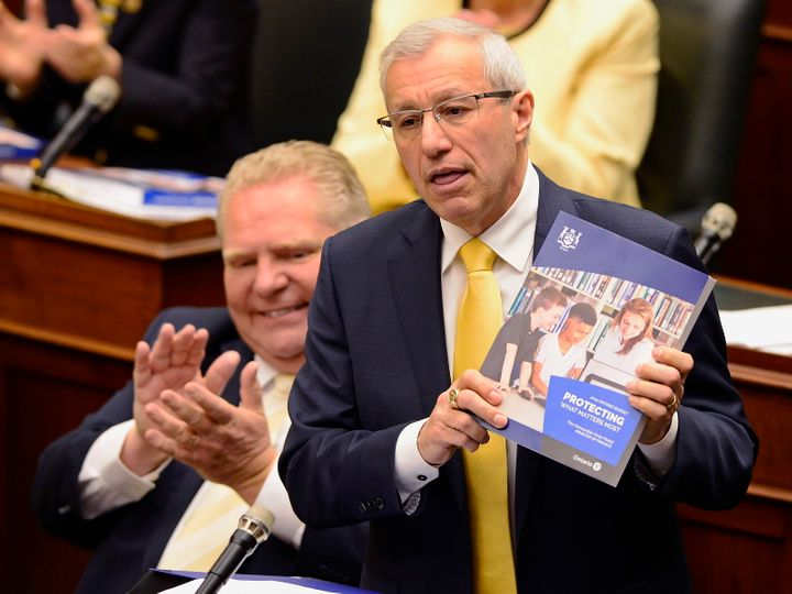 Former finance minister Vic Fedeli presents the 2019 budget as Premier Doug Ford looks on at the legislature in Toronto on April 11, 2019.
