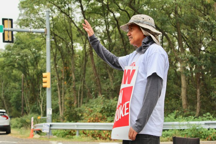 Joel Inocencio waves to a supporter outside the Langhorne GM facility.