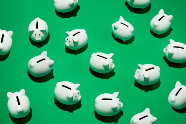 16 small white piggy banks placed randomly on green surface, high angle of