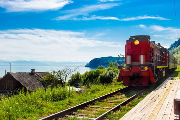 Landscape for travel with the arrival of a red train on a wooden deserted platform Circum-Baikal railway...